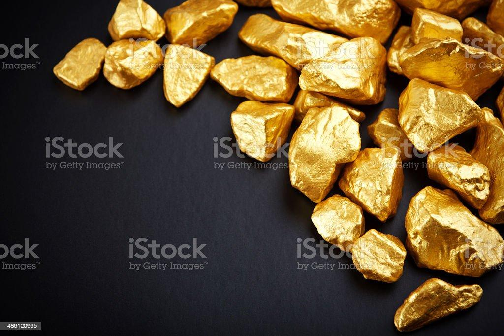 Pepitas de ouro em um preto plano. detalhe. - foto de acervo