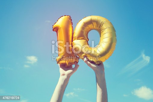 A gold foil number 10 balloon is held high in the air by caucasian male hand.  The image has been taken outdoors on a bright sunny day, the sky is blue with some clouds. A vintage style effects has been added to the image.