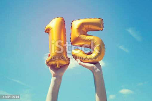 A gold foil number 15 balloon is held high in the air by caucasian male hand.  The image has been taken outdoors on a bright sunny day, the sky is blue with some clouds. A vintage style effects has been added to the image.