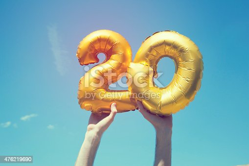 A gold foil number 20 balloon is held high in the air by caucasian male hand.  The image has been taken outdoors on a bright sunny day, the sky is blue with some clouds. A vintage style effects has been added to the image.