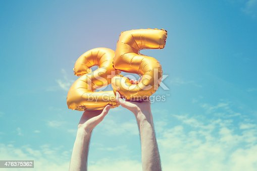 A gold foil number 25 balloon is held high in the air by caucasian male hand.  The image has been taken outdoors on a bright sunny day, the sky is blue with some clouds. A vintage style effects has been added to the image.