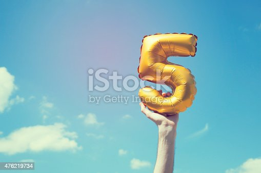 A gold foil number 5 balloon is held high in the air by caucasian male hand.  The image has been taken outdoors on a bright sunny day, the sky is blue with some clouds. A vintage style effects has been added to the image.
