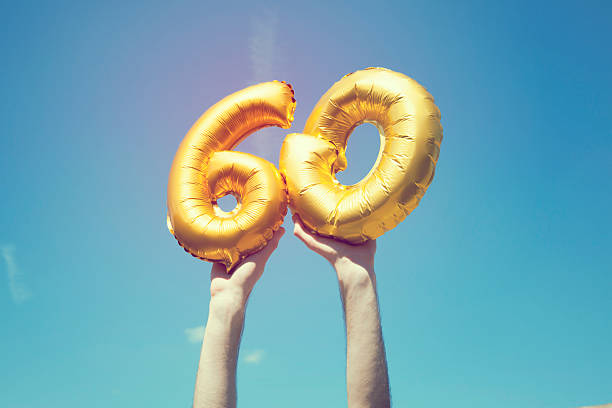 Gold number 60 balloon A gold foil number 60 balloon is held high in the air by caucasian male hand.  The image has been taken outdoors on a bright sunny day, the sky is blue with some clouds. A vintage style effects has been added to the image. 60 64 years stock pictures, royalty-free photos & images