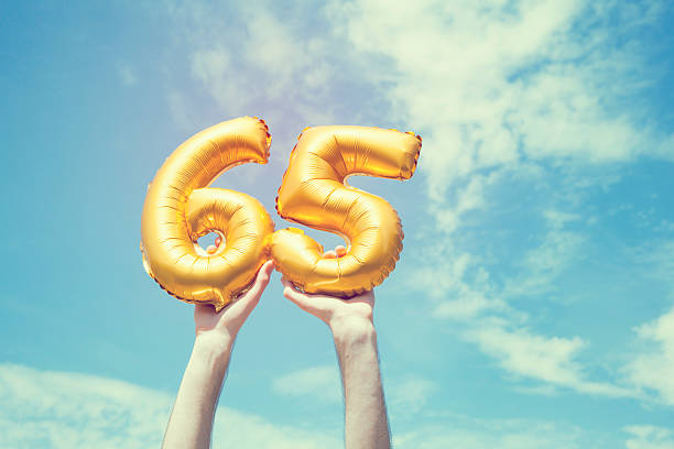 Gold number 65 balloon A gold foil number 65 balloon is held high in the air by caucasian male hand.  The image has been taken outdoors on a bright sunny day, the sky is blue with some clouds. A vintage style effects has been added to the image. 65 69 years stock pictures, royalty-free photos & images