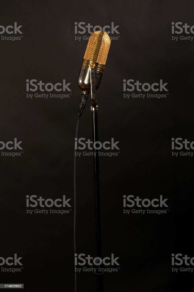 gold old school microphone from side stock photo