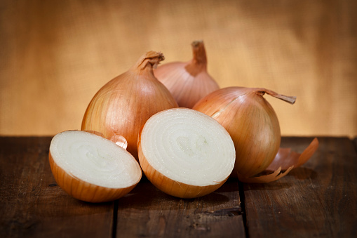 Still life of three gold onions on a wooden table, the one on the foreground it is cut in halves. Predominant color is brown. DSRL studio photo taken with Canon EOS 5D Mk II and Canon EF 70-200mm f/2.8L IS II USM Telephoto Zoom Lens