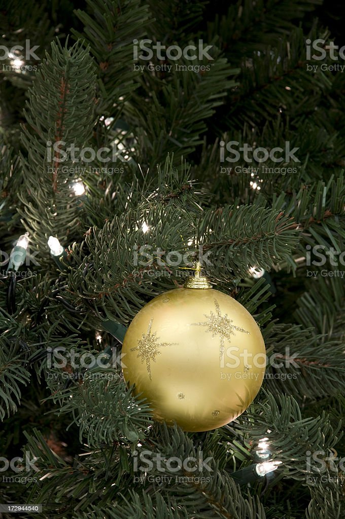 Gold ornament on Christmas tree stock photo