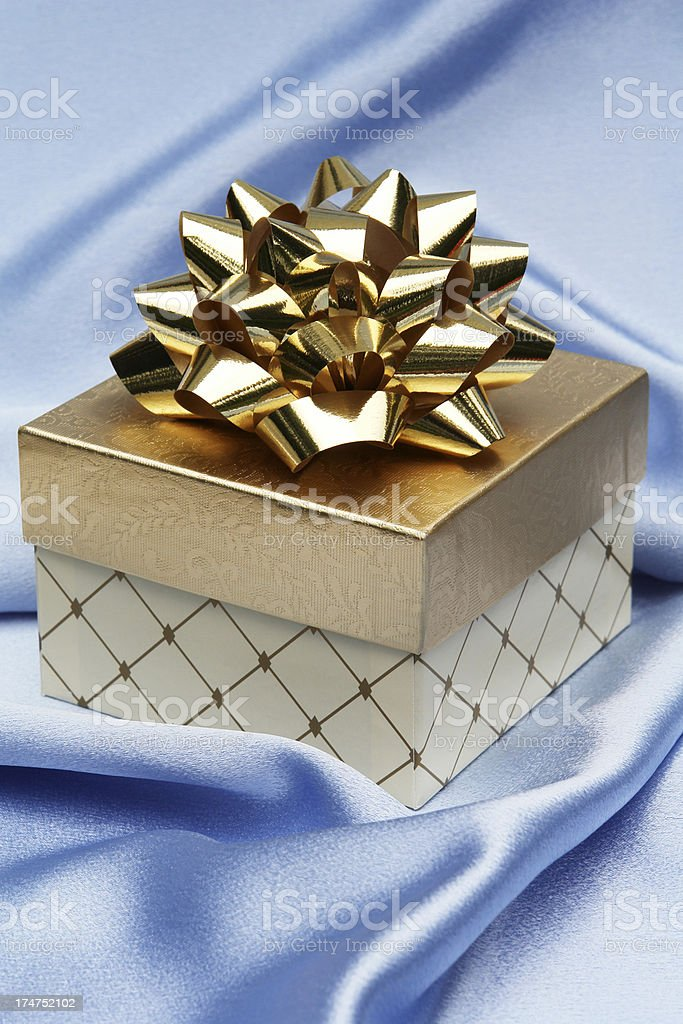 Gold package and bow on blue satin royalty-free stock photo