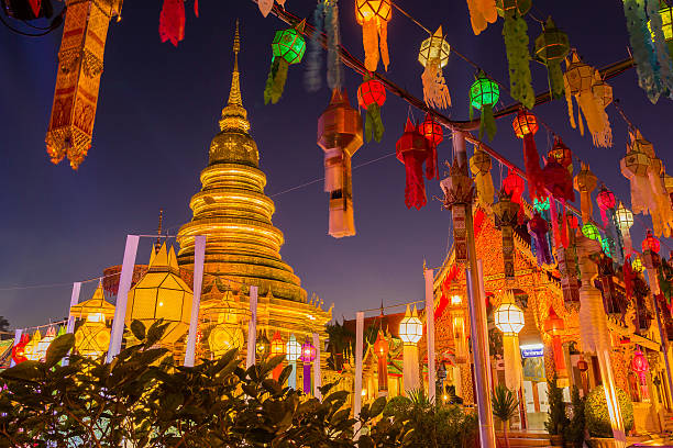 Gold pagoda and lantern hung up on the rail Gold pagoda and lantern hung up on the rail to the prosperity in loy kratong festival at wat phra that haripunchai lamphun Thailand at night time chiang mai province stock pictures, royalty-free photos & images