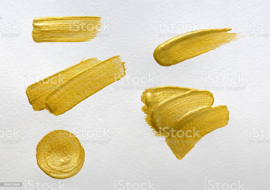 Gold paint stokes on white watercolor paper background stock photo