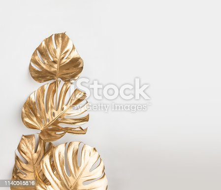 istock Gold painted monstera leaves on white background 1140015816