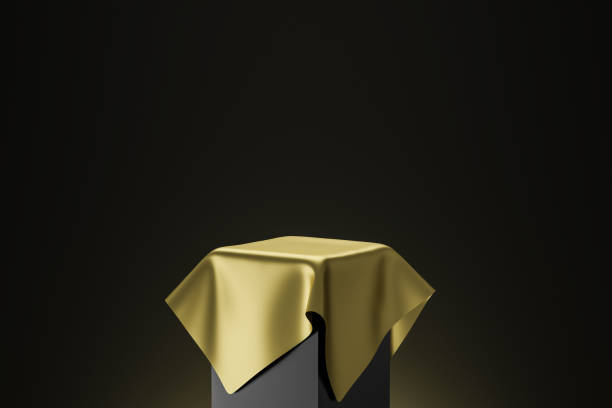 Gold pedestal or podium display with golden satin fabric platform concept on dark background. Blank shelf stand for showing product. 3D rendering. stock photo
