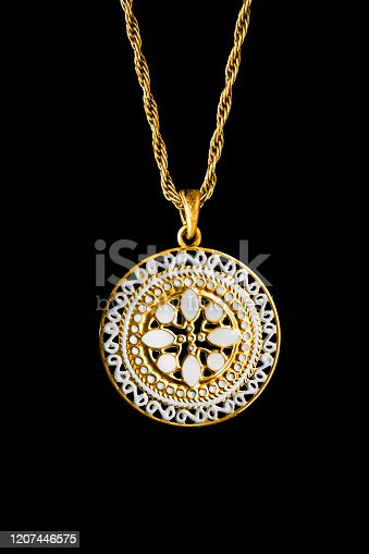 Ethnic gold carved pendant hanging on a chain isolated over black