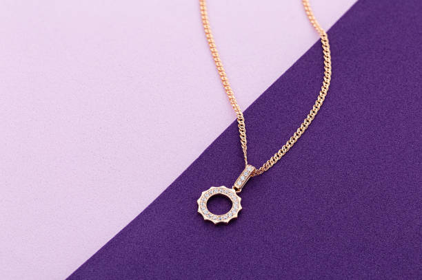 Gold pendant necklace with diamonds on pink and purple background