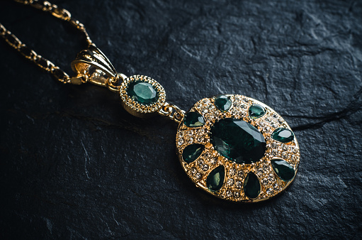 Gold pendant with green emeralds on a black stone background close up