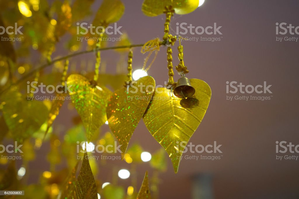 Gold pho leaves hanging on golden tree stock photo