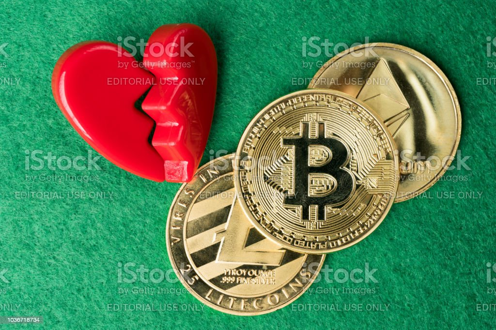 Gold physical Bitcoin, Litecoin and Ethereum coins with broken heart. stock photo