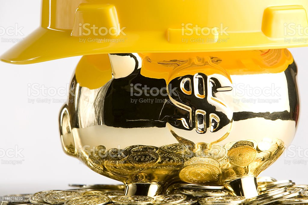 Gold piggy bank with a construction hard hat royalty-free stock photo
