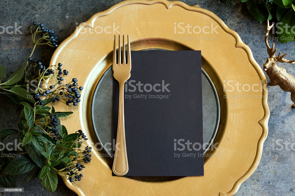 Gold place setting with empty menu on grunge stock photo