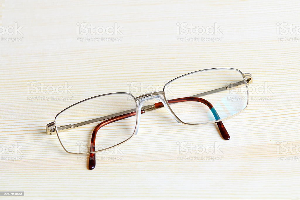 Gold plated mens glasses on a table top stock photo