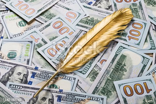 istock Gold quill pen on dollar money background 1142183743