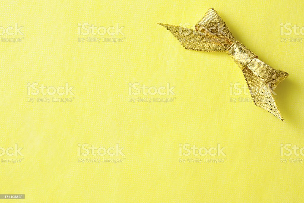 Gold ribbon bow on yellow wrapping paper with copy space royalty-free stock photo