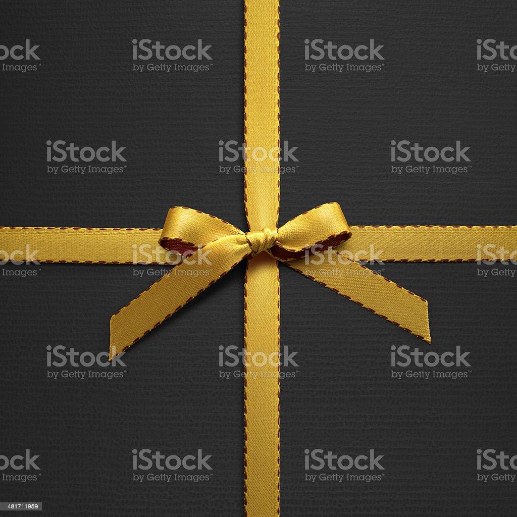Gold ribbon on black paper stock photo