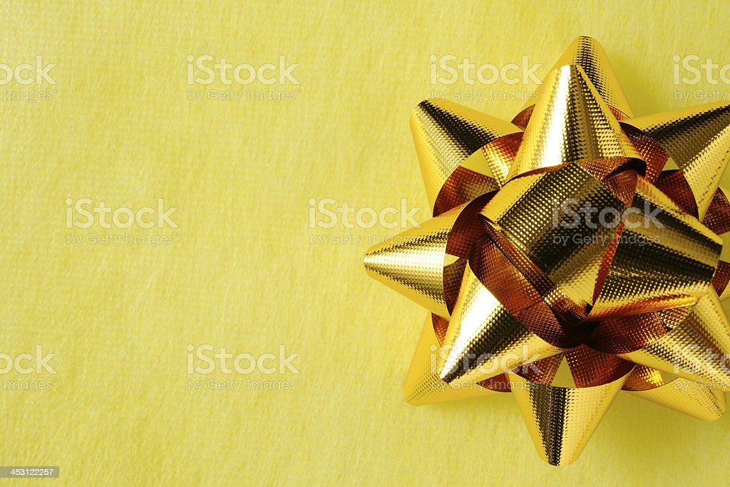 Gold ribbon on yellow wrapping paper with copy space royalty-free stock photo