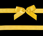 istock Gold ribbon with bow isolated on black. Clipping path included. 869829306