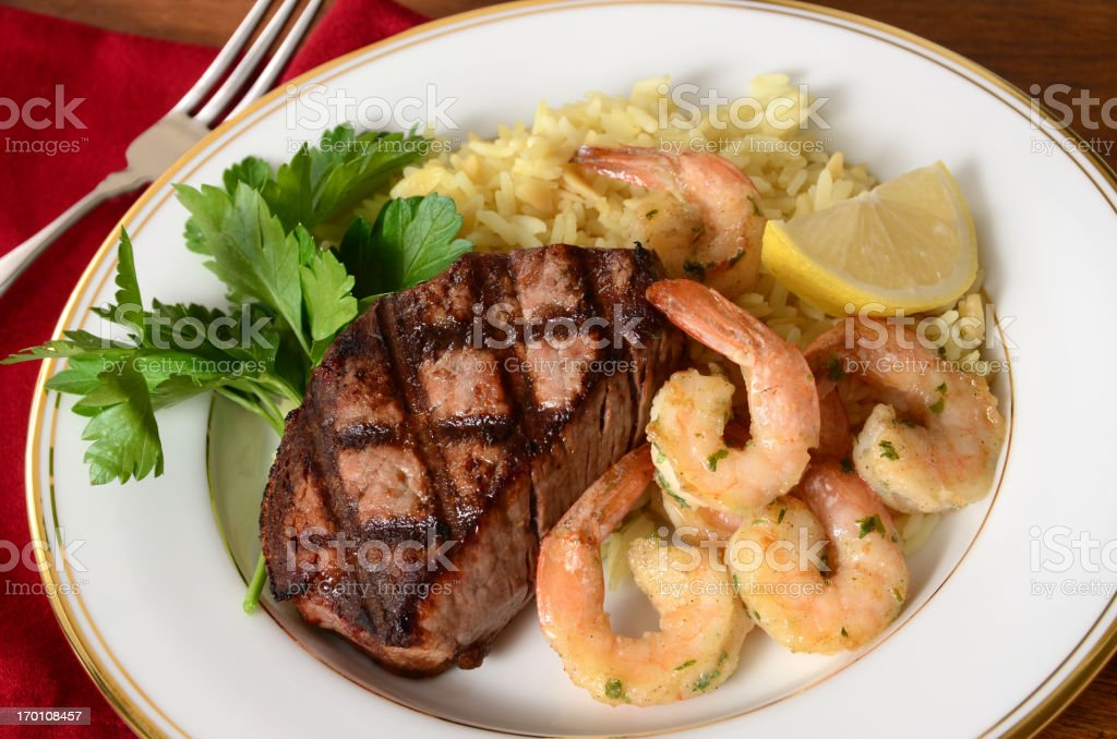 Gold rimmed, white China dish with steak and shrimp scampi royalty-free stock photo