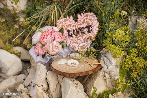 wedding gold rings and hand bouquet arrangement and love letter in seashells on wooden floor on cliffs
