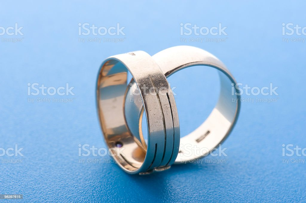 Gold rings on blue background macro royalty-free stock photo