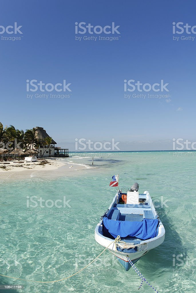 Gold sand, blue water and a boat royalty-free stock photo