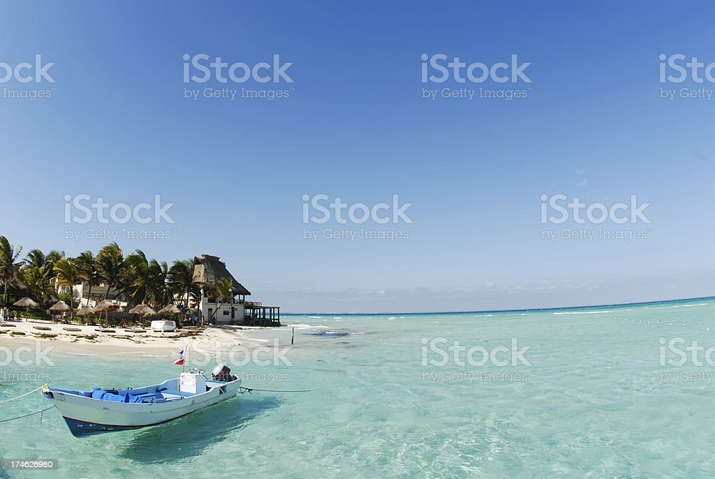 Gold sand, blue water and a boat stock photo