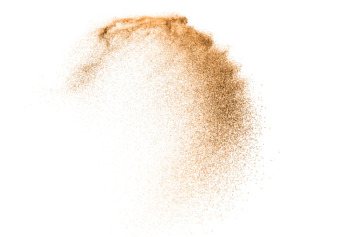 Gold sand explosion isolated on white background. Abstract sand cloud. Gold sand splash against on clear background. Sandy fly wave in the air.