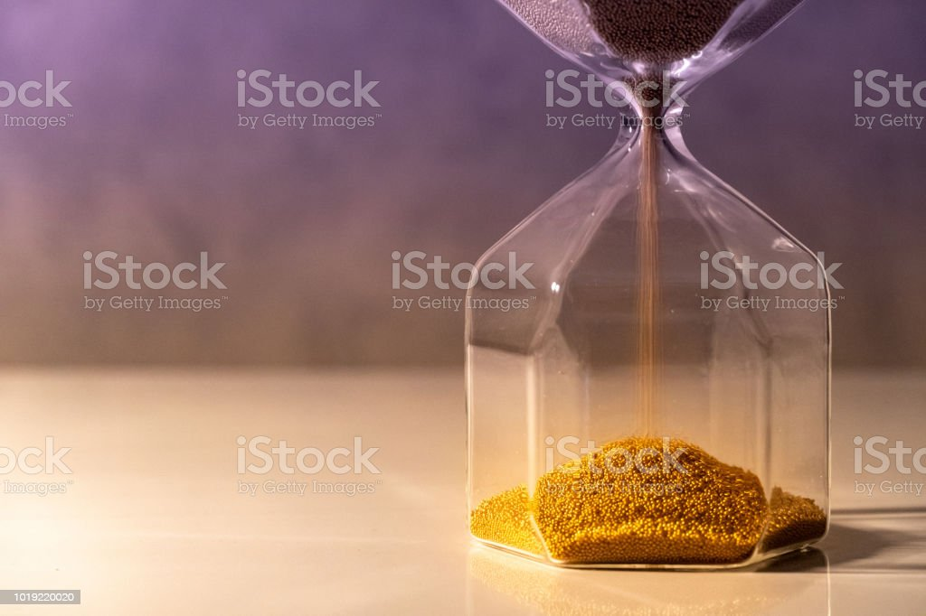 Gold sand running through the shape of modern hourglass on white table.Time passing and running out of time. Urgency countdown timer for business deadline concept stock photo