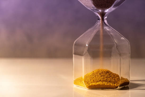 Gold sand running through the shape of modern hourglass on white table.Time passing and running out of time. Urgency countdown timer for business deadline concept Gold sand running through the shape of modern hourglass on white table.Time passing and running out of time. Urgency countdown timer for business deadline concept patience stock pictures, royalty-free photos & images