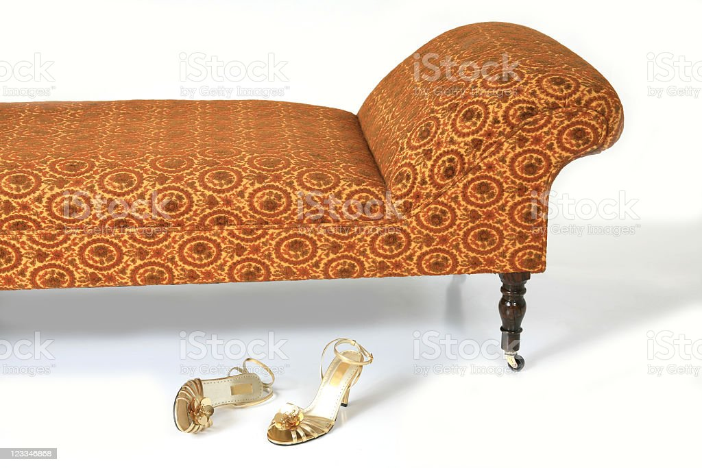 Gold sandals by couch stock photo
