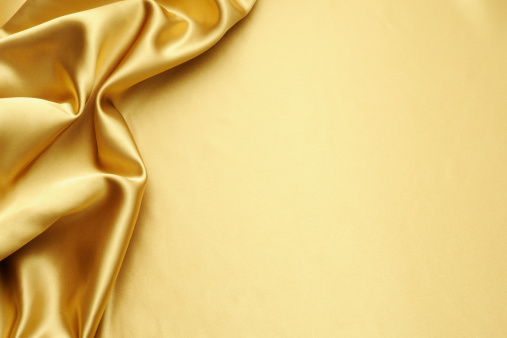 Close-up shot of gold satin texture backgrounds with copy space.