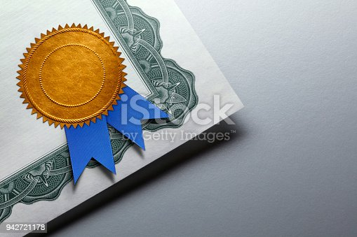 A close up of a gold seal adorned with a blue ribbon is attached to the corner of a certificate of achievement which rests on top of a gray background which provides ample room for copy or text.