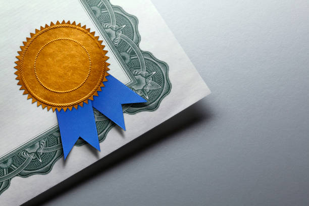 gold seal with blue ribbon on a certificate of achievement - diploma stock photos and pictures