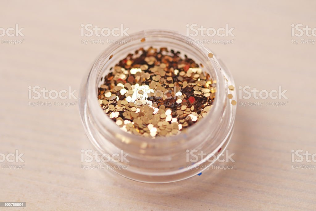 Gold Sequins for the design of nails in a box. Glitter in jars. Foil for nail service. Photo set. Sparkling beauty shimmer, glitter - Royalty-free Arranging Stock Photo