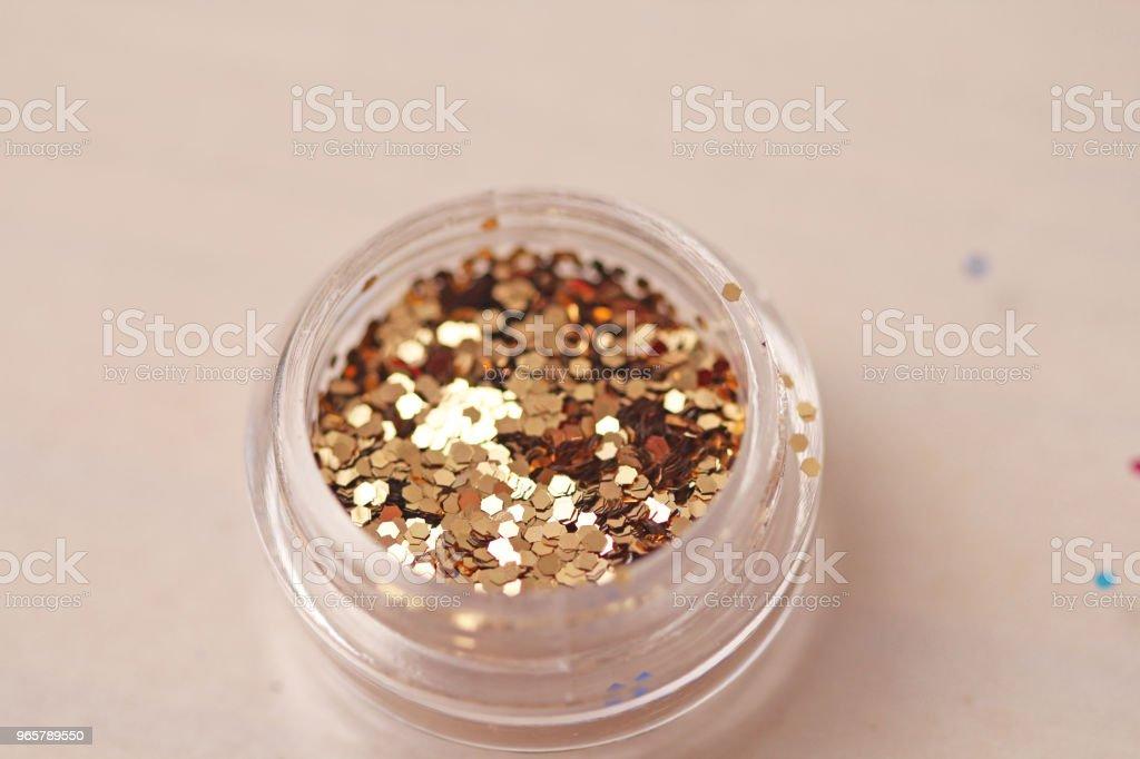 Gouden pailletten voor het ontwerp van de nagels in een doos. Glitter in potten. Folie voor nagel service. Foto set. Sprankelende schoonheid shimmer, glitter - Royalty-free Bewogen - Beeldtechniek Stockfoto