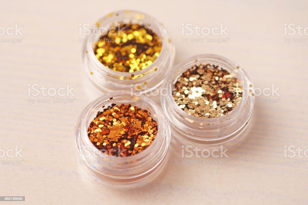 Gouden pailletten voor het ontwerp van de nagels in een doos. Glitter in potten. Folie voor nagel service. Foto set. Sprankelende schoonheid shimmer, glitter - Royalty-free Bontgekleurd Stockfoto