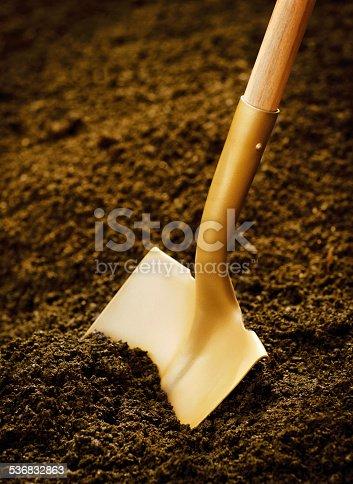 Gold shovel in dirt.