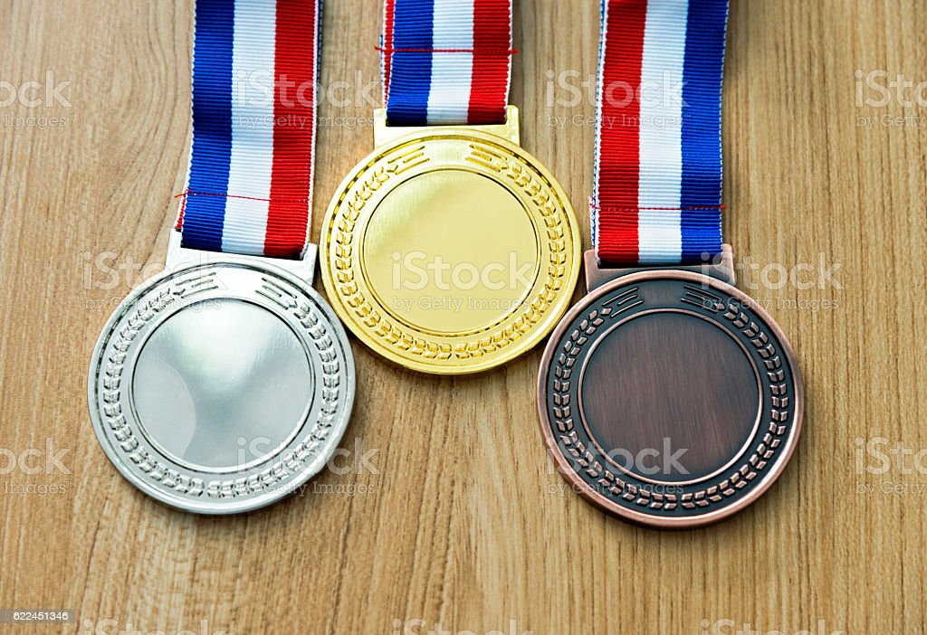 Gold, silver, and bronze medal on wood desk stock photo