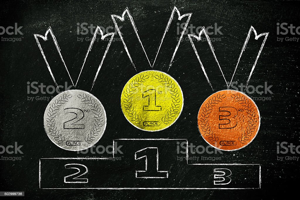 gold, silver and bronze medals on podium stock photo