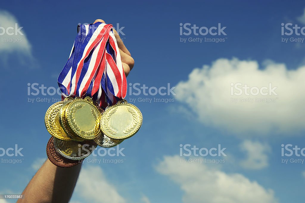 Gold Silver Bronze Medals Hand Holding Up in Blue Sky stock photo