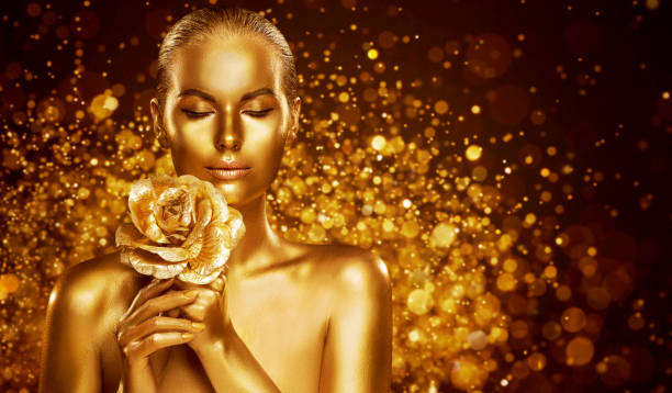 Gold Skin Body Art, Golden Woman Beauty Portrait with Flower, Fashion Make Up stock photo