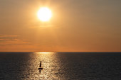 A golden sunset casts a beam of light on a small boat on Lake Huron in Bayfield Ontario